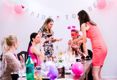 Jeune mariée gaie et demoiselles d'honneur célébrant la partie de poule avec des boissons Images stock