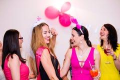 Jeune mariée gaie et demoiselles d'honneur célébrant la partie de poule avec des boissons Photos libres de droits
