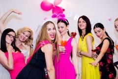 Jeune mariée gaie et demoiselles d'honneur célébrant la partie de poule avec des boissons Images libres de droits