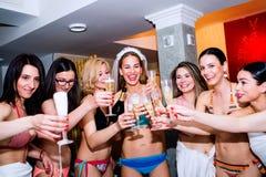 Jeune mariée gaie et demoiselles d'honneur célébrant la partie de poule avec le champa Images stock