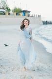 Jeune mariée gaie faisant une promenade le long de la plage Photographie stock libre de droits