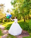 Jeune mariée gaie posant avec le groupe de ballons Photos libres de droits