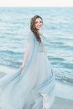 Jeune mariée gaie tournant autour au bord de la mer Photos stock