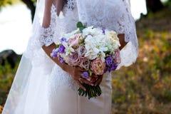 Jeune mariée gracieuse tenant le bouquet de mariage Images libres de droits