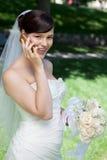 Jeune mariée heureuse à l'aide du téléphone portable Photographie stock libre de droits