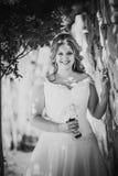 Jeune mariée heureuse élégante de photographie blanche noire belle tenant le bouquet des fleurs sur un mur en pierre de fond Photo libre de droits