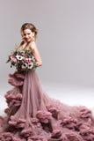 Jeune mariée heureuse avec le bouquet de fleur dans la robe rose Images libres de droits