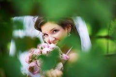 Jeune mariée heureuse avec les pivoines roses épousant le bouquet Photographie stock libre de droits