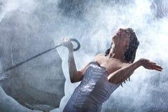 Jeune mariée heureuse avec le parapluie sur la grande pluie Photo stock