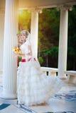 Jeune mariée heureuse dans la robe blanche près du fléau blanc photo stock