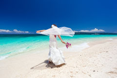 Jeune mariée heureuse de danse sur la plage Photo stock