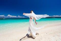 Jeune mariée heureuse de danse sur la plage Image libre de droits