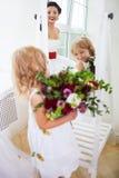 Jeune mariée heureuse de sourire et une demoiselle d'honneur à l'intérieur Image libre de droits