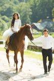 Jeune mariée heureuse magnifique de brune montant un cheval et élégant élégants Photos libres de droits