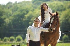 Jeune mariée heureuse magnifique de brune montant un cheval et élégant élégants Photographie stock