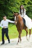 Jeune mariée heureuse magnifique de brune montant un cheval et élégant élégants Images libres de droits