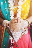 Jeune mariée indienne avec des bracelets sur son poignet jugeant le shagun de noix de coco nariyal pour le rituel indien de maria photos stock