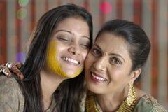Jeune mariée indoue indienne avec la pâte de safran des indes sur le visage étreignant la mère. Photo stock