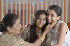 Jeune mariée indoue indienne avec la pâte de safran des indes sur le visage avec la mère et la soeur. image libre de droits