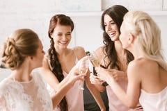 Jeune mariée joyeuse et demoiselles d'honneur ayant la partie à la maison Photos libres de droits