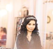 Jeune mariée magnifique élégante obtenant le maquillage dans la salle de luxe de beauté avec de grands miroirs et lumière Photo libre de droits