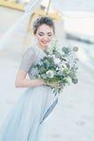 Jeune mariée magnifique avec le bouquet de mariage par la mer Photos stock