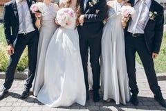 Jeune mariée magnifique avec le bouquet de pivoine et marié élégant posant au su Photographie stock