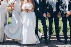 Jeune mariée magnifique avec le bouquet de pivoine et marié élégant posant au su Photo stock