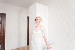 Jeune mariée magnifique avec le maquillage et la coiffure de bouquet de mariage dans la robe nuptiale à la maison attendant le ma Images libres de droits