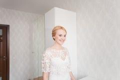 Jeune mariée magnifique avec le maquillage et la coiffure de bouquet de mariage dans la robe nuptiale à la maison attendant le ma Photographie stock