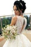 Jeune mariée magnifique avec les cheveux foncés à la robe de mariage luxueuse et au CRNA photo stock