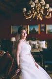 Jeune mariée magnifique dans la robe de mariage dans l'intérieur de luxe avec les bijoux de diamant posant à la maison et le mari Images libres de droits