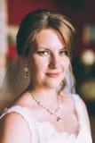 Jeune mariée magnifique dans la robe de mariage dans l'intérieur de luxe avec les bijoux de diamant posant à la maison et le mari Photographie stock