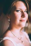 Jeune mariée magnifique dans la robe de mariage dans l'intérieur de luxe avec les bijoux de diamant posant à la maison et le mari Photo stock