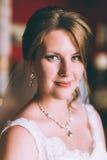 Jeune mariée magnifique dans la robe de mariage dans l'intérieur de luxe avec les bijoux de diamant posant à la maison et le mari Photo libre de droits