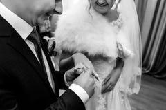 Jeune mariée magnifique heureuse et marié élégant échangeant des anneaux de mariage Photos stock