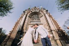 Jeune mariée magnifique heureuse et marié beau élégant embrassant sur le fond de l'église étonnante de bâtiment dans la ville Photos libres de droits