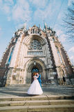 Jeune mariée magnifique heureuse et marié beau élégant sur le fond d'une église étonnante de bâtiment dans la ville Photo libre de droits
