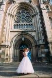 Jeune mariée magnifique heureuse et marié beau élégant sur le fond d'une église étonnante de bâtiment dans la ville Photo stock
