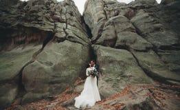 Jeune mariée magnifique, marié embrassant et étreignant près des falaises avec des vues renversantes images libres de droits