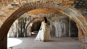Jeune mariée marchant sous des voûtes de brique clips vidéos