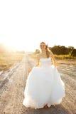 Jeune mariée marchant sur une route de campagne photos stock