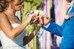Jeune mariée mettant l'anneau de mariage sur la main du ` s de marié photographie stock