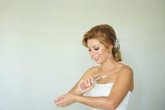 Jeune mariée mettant le parfum sur des mains image stock