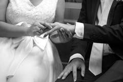 Jeune mariée mettant un anneau de mariage sur le doigt du ` s de marié Images stock