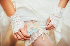 Jeune mariée mettant une jarretière de mariage sur sa jambe Photo stock