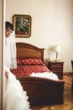 Jeune mariée mignonne dans la robe de mariage posant sur le lit de fond Photos stock