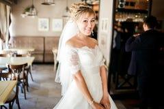 Jeune mariée mignonne dans une robe de mariage au café Photographie stock