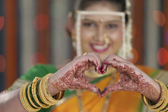 Jeune mariée montrant la forme de coeur avec des mains dans le mariage indou indien Photos libres de droits