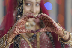 Jeune mariée montrant la forme de coeur avec des mains dans le mariage indou indien Images libres de droits